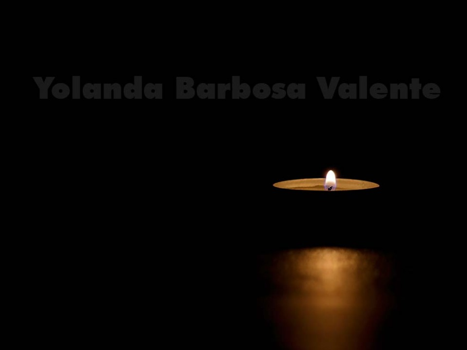 A lit tin candle in the dark conveying memorial, death, hope or darkness